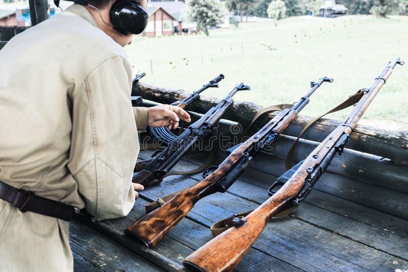 Bij de het schieten waaier militaire herladen automatische machine om te schieten er zijn het stemmen stock foto's