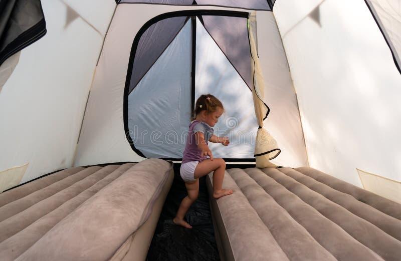 Bij het kampeerterrein, springt een klein meisje in een tent op matrassen royalty-vrije stock afbeelding