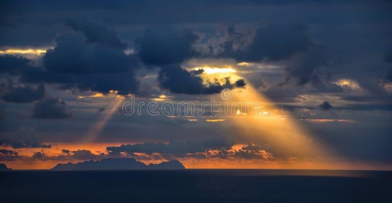 Bij zonsopgang, glanzen de zonstralen door de wolken aan de oceaan royalty-vrije stock afbeeldingen