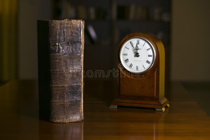 Bijbel en klok stock afbeeldingen