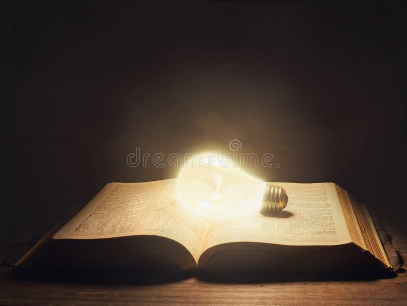 Bijbel met gloeilamp stock afbeeldingen