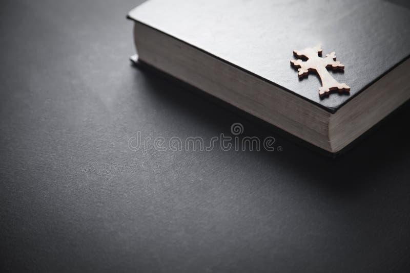 Bijbel met houten kruis op zwarte achtergrond stock afbeelding