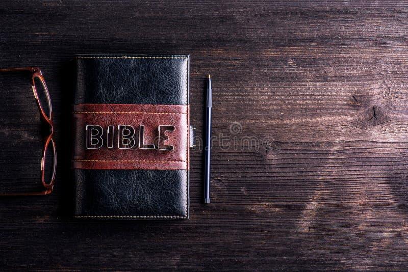 Bijbel, oogglazen en pen op oude houten lijst wordt gelegd die stock afbeelding