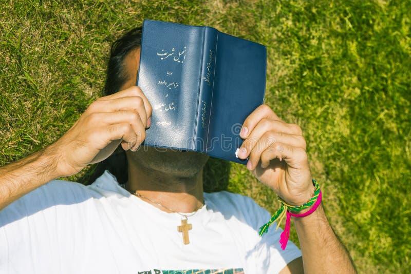 Bijbel van de jonge Mensen de ex-Moslimlezing buiten royalty-vrije stock afbeelding
