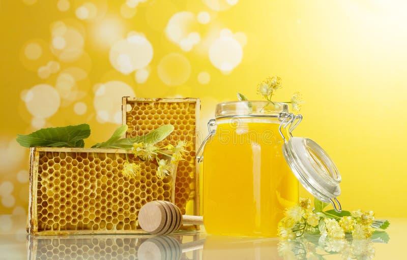 Bijen houten kader, kruik met honing en as op gele achtergrond royalty-vrije stock afbeeldingen