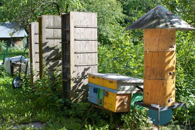 Bijenstal in de bloeiende tuin eigengemaakte bijenkorven stock foto