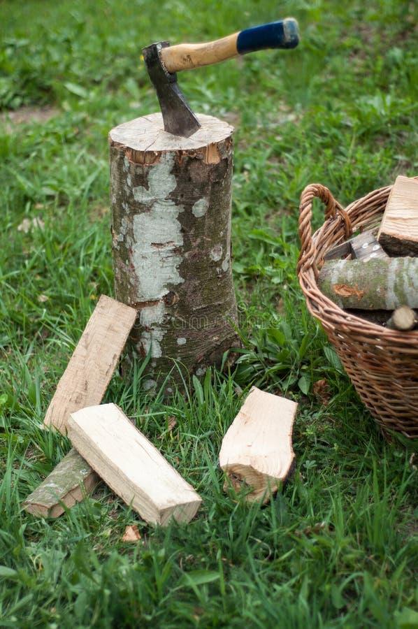 Bijl en houten bomenlogboeken na wordt gesneden op gras royalty-vrije stock foto's