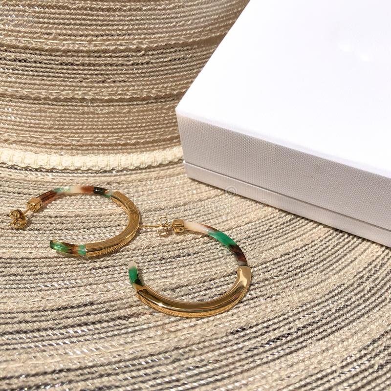 Bijou hoops. Big golden tone fashion hoops laying on beige summer hat next to white box royalty free stock photography