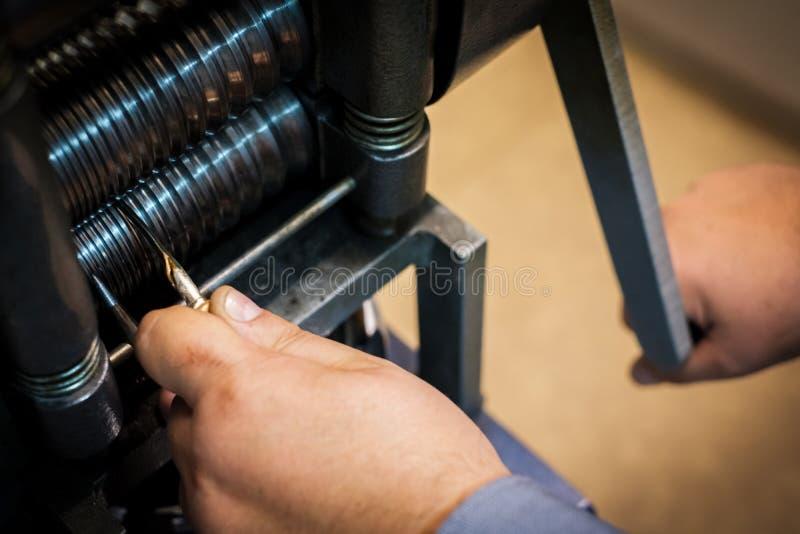 Bijoutier formant un argent ou un or de morceau dans la presse de petit pain photo stock