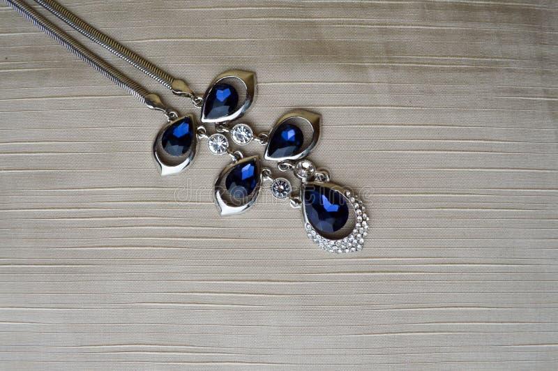 Bijoux argentés femelles avec les gemmes bleues, diamants sur un fond beige dans le coin gauche supérieur photographie stock libre de droits
