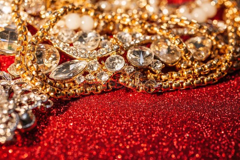 Bijoux d'or et argentés sur le fond brillant rouge de scintillement image libre de droits