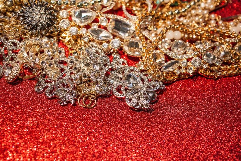 Bijoux d'or et argentés sur le fond brillant rouge de scintillement image stock