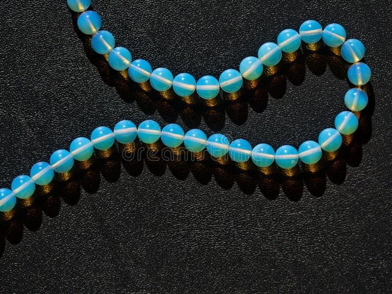 Bijoux de colliers faits avec la pierre de lune sur le fond de relief noir image stock