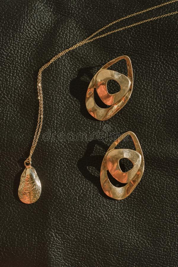 Bijoux de l'or des femmes élégantes et bijoux sur un fond en cuir Pendant et boucles d'oreille à la mode photos libres de droits