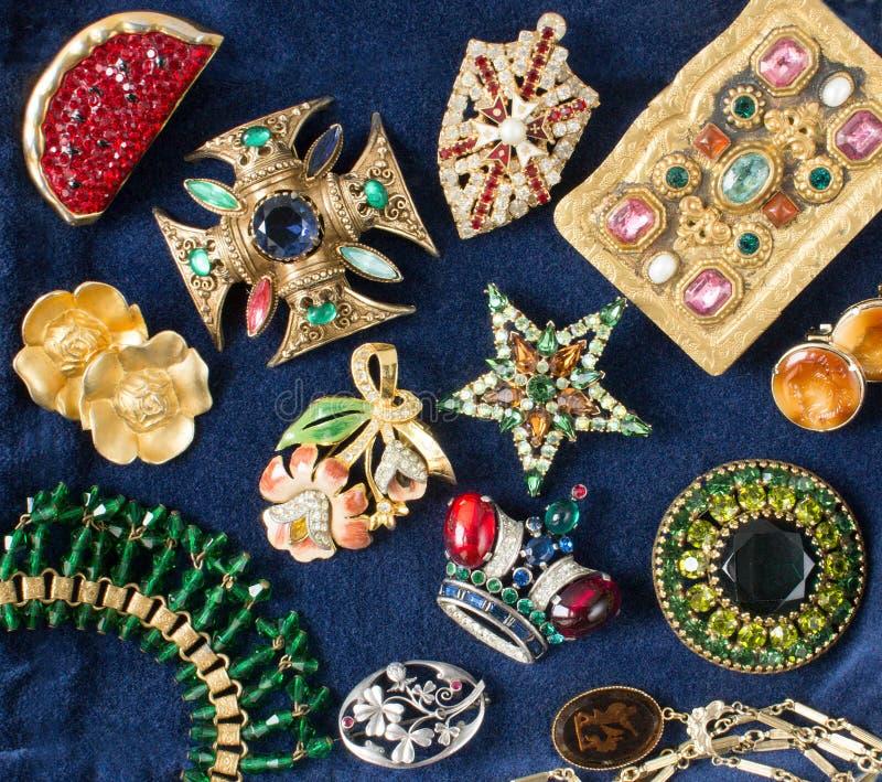 Bijoux du ` s de femme Fond luxueux de bijoux de cru Belles broches et boucles d'oreille de fausses pierres sur le fond bleu de v image libre de droits