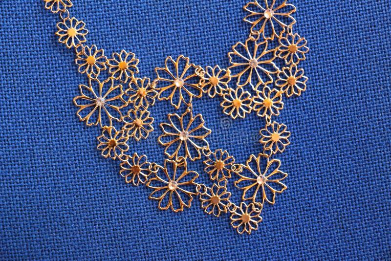 Bijoux kolia na błękitnym tkaniny tle obrazy stock