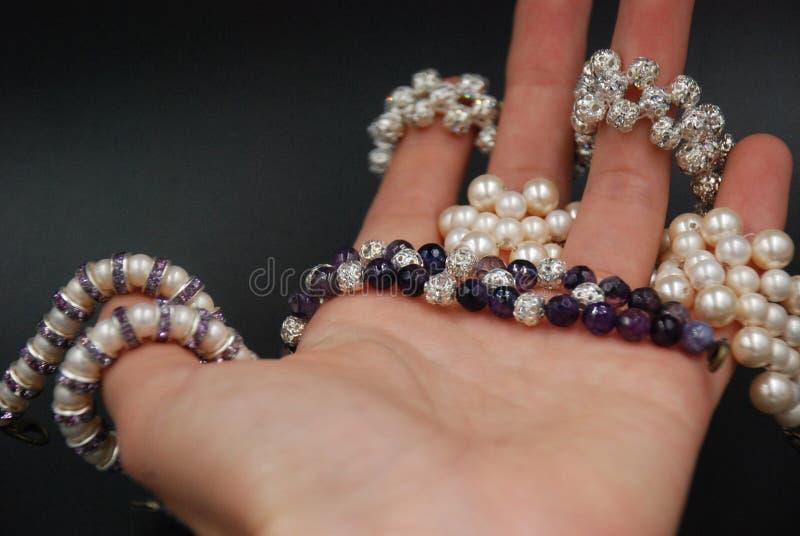 Bijoux perlés des perles et des cristaux sur la main photographie stock libre de droits