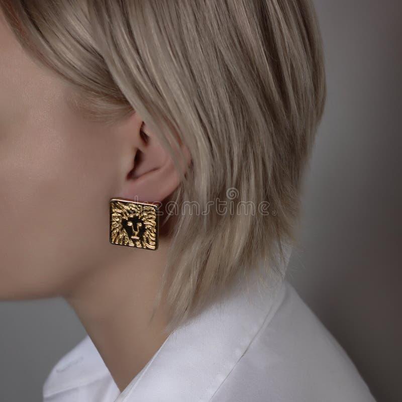 Bijoux sous forme de boucles d'oreille sur la fin de l'oreille de la fille  photo libre de droits