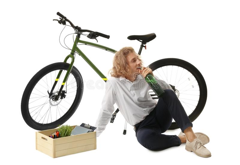 Bijste jongeman met fles wijn en hokje bezittingen in de buurt van fiets op wit stock foto