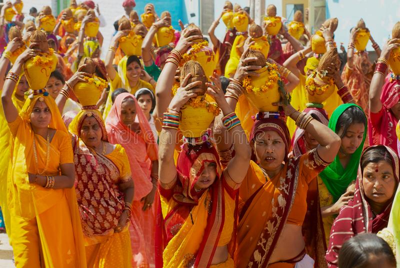 Rajasthani women wearing yellow and red sarees holding coconuts and pots take part in a religious procession in Bikaner, India. Bikaner, India, April 01, 2007 stock photo