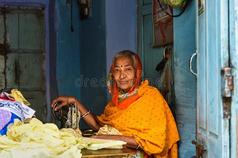 Indian woman tailor at work place with sewing machine in Bikaner. Rajasthan. India royalty free stock photo