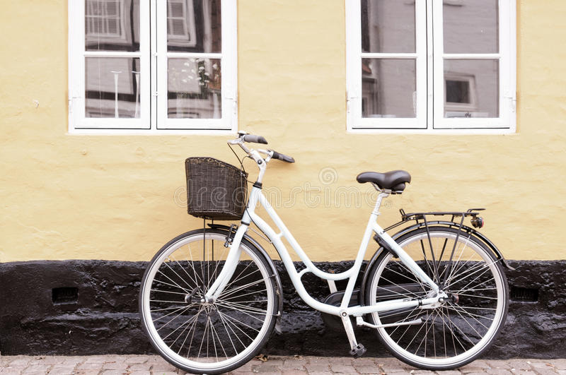 Bike. Vintage bike with basket against wall in Denmark in sepia tone royalty free stock image