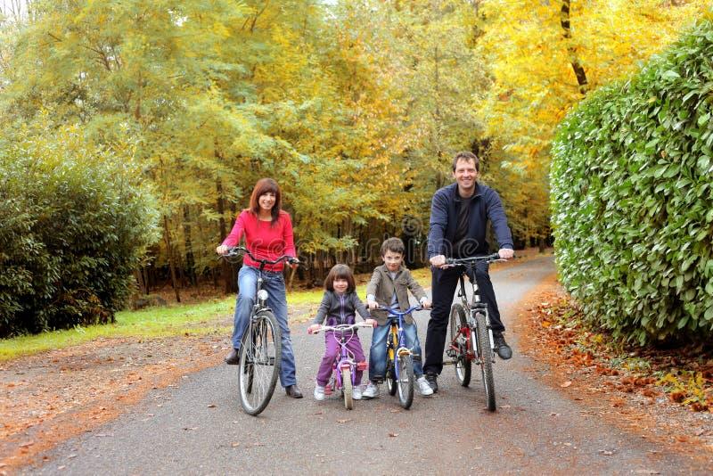 Bike. Happy family riding bike in a park stock image