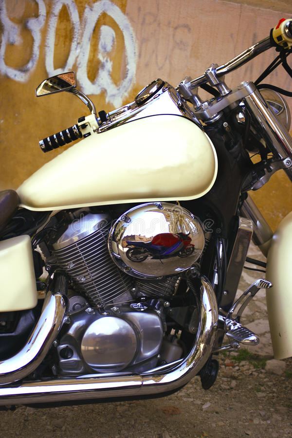 The Bike. A detail of a powerful motorcycle with engine in foreground and a nice reflection visible on the polished metal royalty free stock image