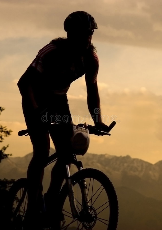 Bike. Silhouette of sportsman and bike at competition in mountain. Sunset royalty free stock images