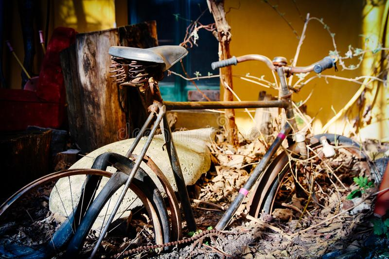 Bike abandoned remaining of rusty retro vintage bicycle half covered by earth. Photo color toned for nostalgic look effect stock image