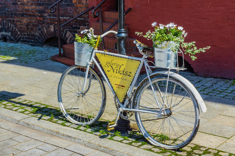 Bike as a signpost and advertisment. Of Nikisz Art Gallery in Nikiszowiec, district of Katowice, Silesia region, Poland, on May 31, 2014. The place is historic royalty free stock photography
