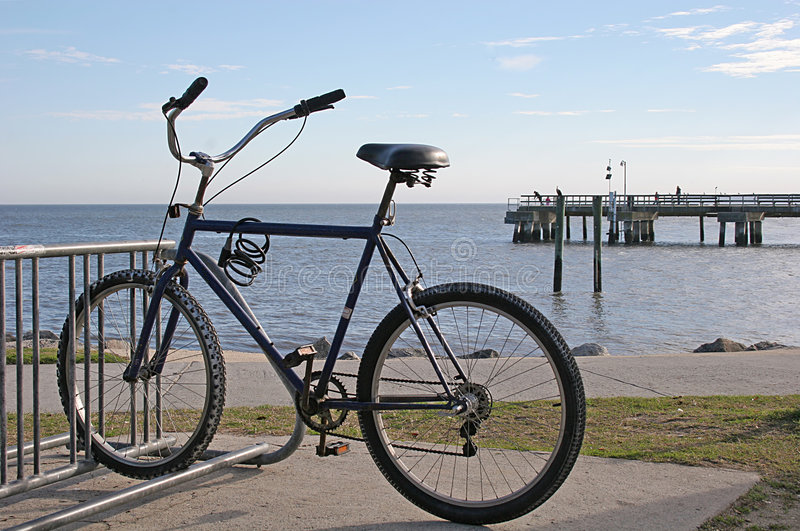 Bike on the Beach. Solitary bike captured against backdrop of beach and pier royalty free stock photo