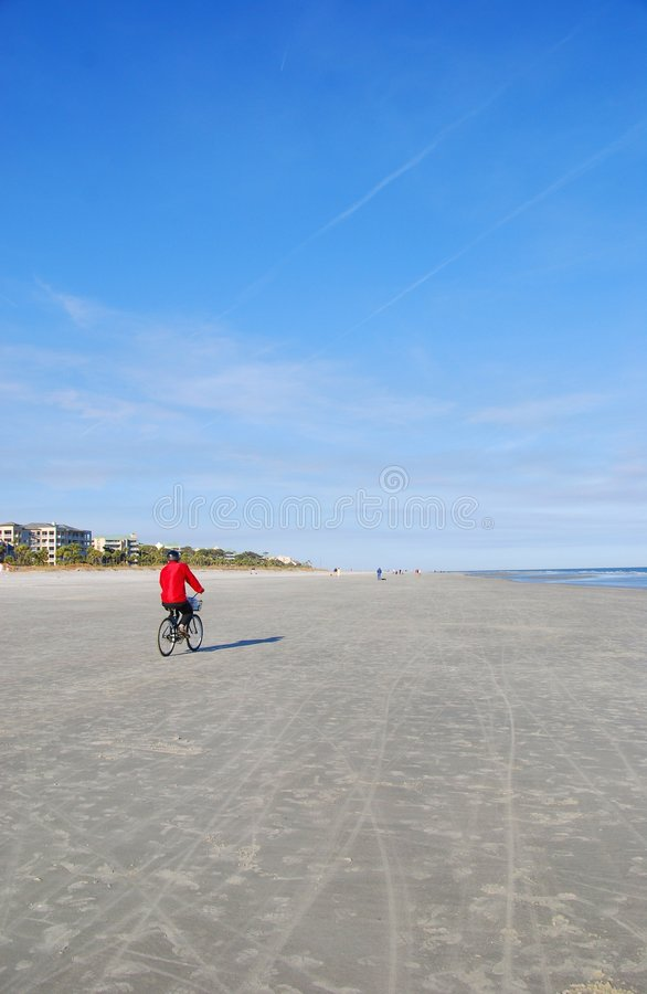 Bike on Beach. A man wearing a bright red jacket rides his bike on an isolated beach stock photos