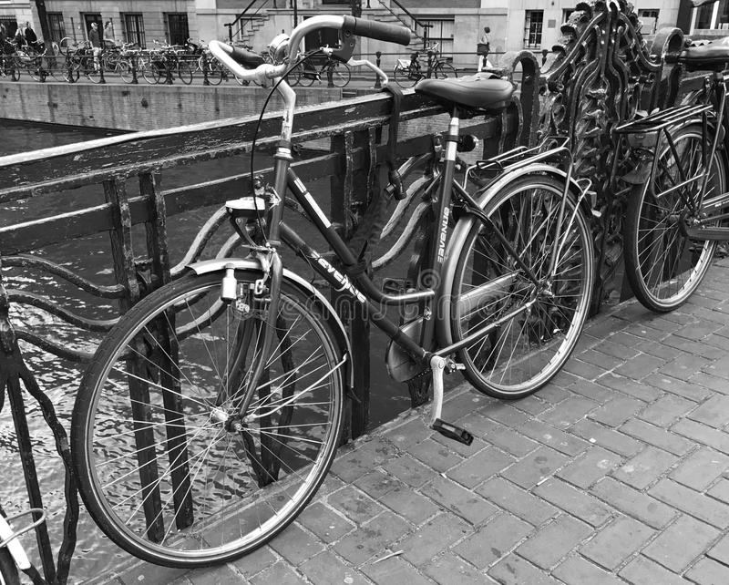 Bike in black and white. Classic Amsterdam scene with a bike chained to ornate metal railings on a bridge over a central city canal in the summer stock image