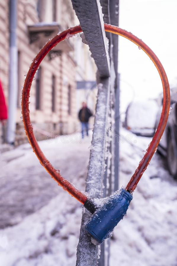 Bike cable lock hanging on the fence during frost, covered with ice royalty free stock photo