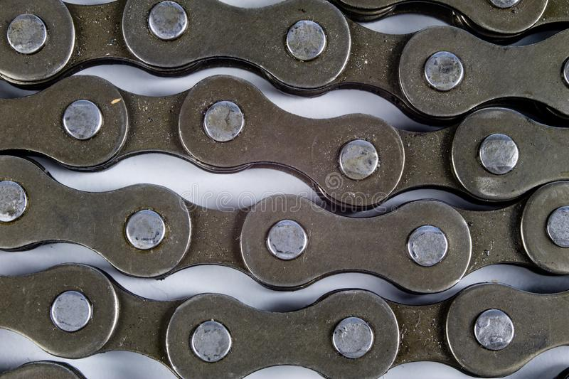Bike chain arranged on a white table. Periodic servicing of part. S for two-wheelers. Light background royalty free stock photography