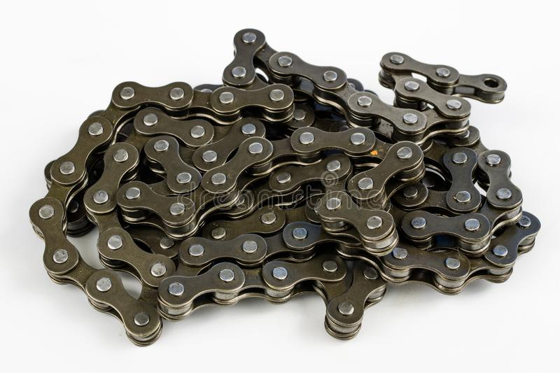 Bike chain arranged on a white table. Periodic servicing of part. S for two-wheelers. Light background stock photo