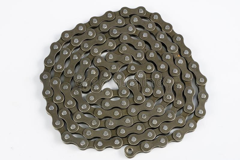 Bike chain arranged on a white table. Periodic servicing of part. S for two-wheelers. Light background stock image