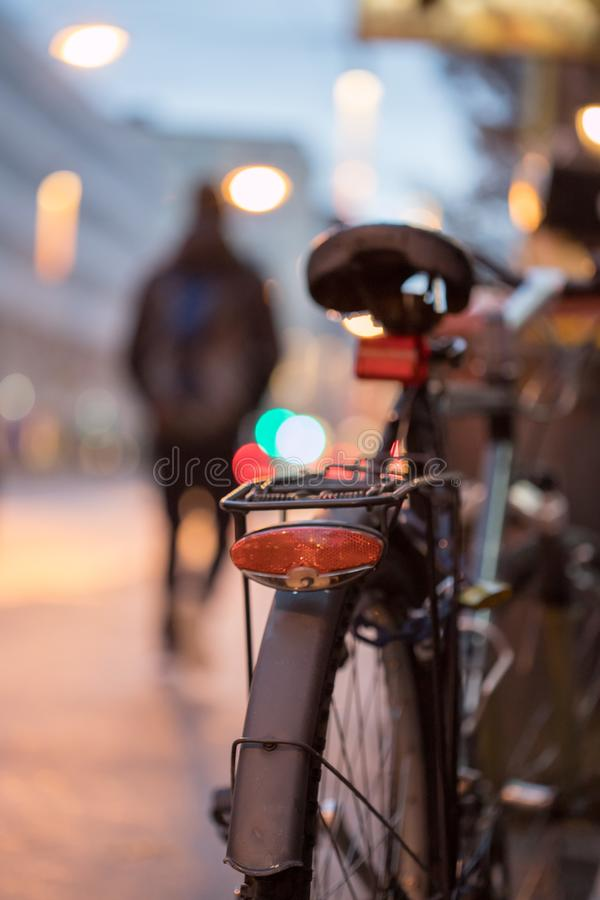 Bike in the city, dusk: Rear picture of a city bike, blurred background. Rear picture of a city bike, blurry background with city lights, evening bicycle royalty free stock images