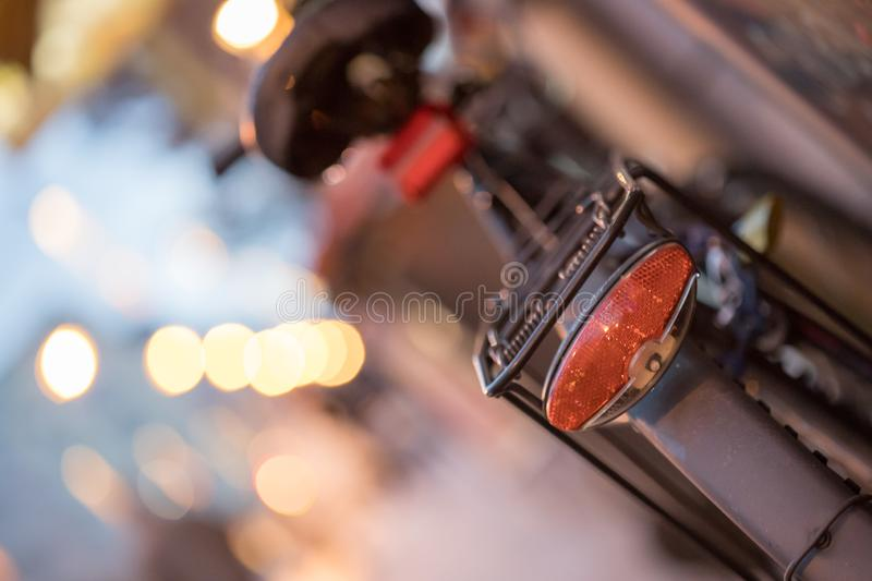 Bike in the city, dusk: Rear picture of a city bike, blurred background. Rear picture of a city bike, blurry background with city lights, evening bicycle royalty free stock photos