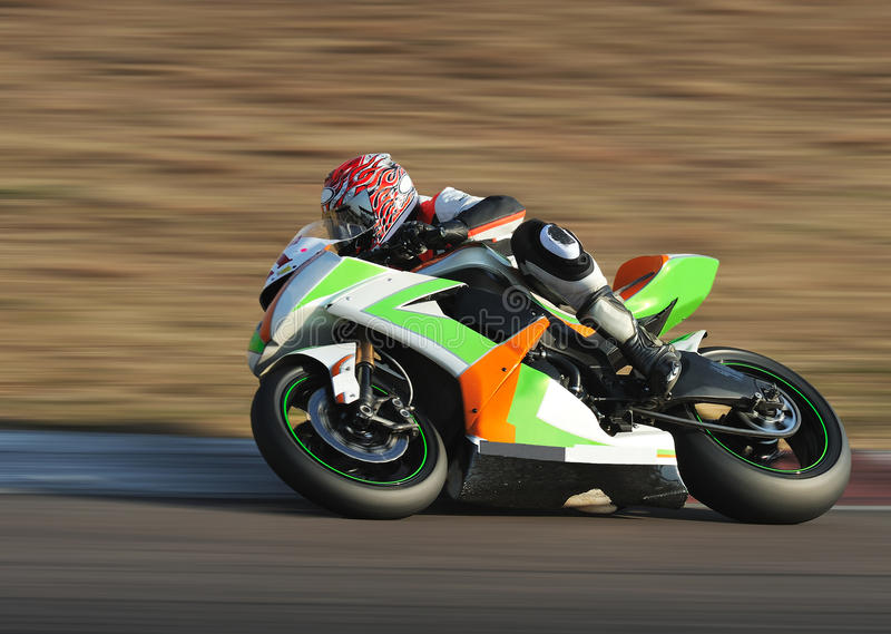 Bike Cornering at Full Speed. Motorcycle racing around corner on the track at high speed. Panned at 1/125s stock image