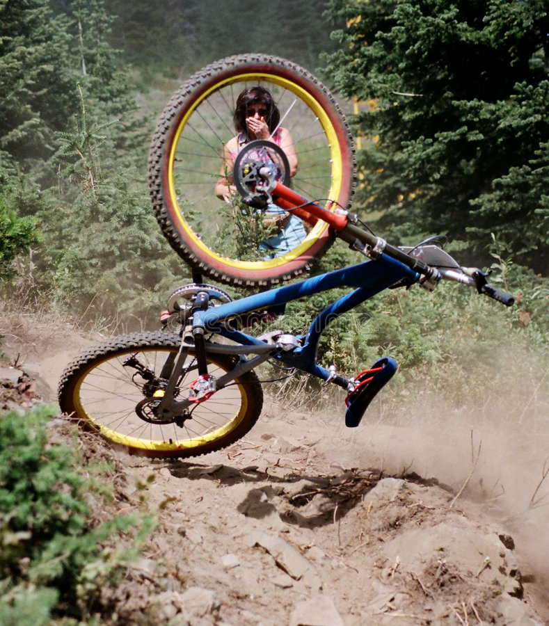 Bike crash. Woman gasping as mountain bike crashes in front of her stock image