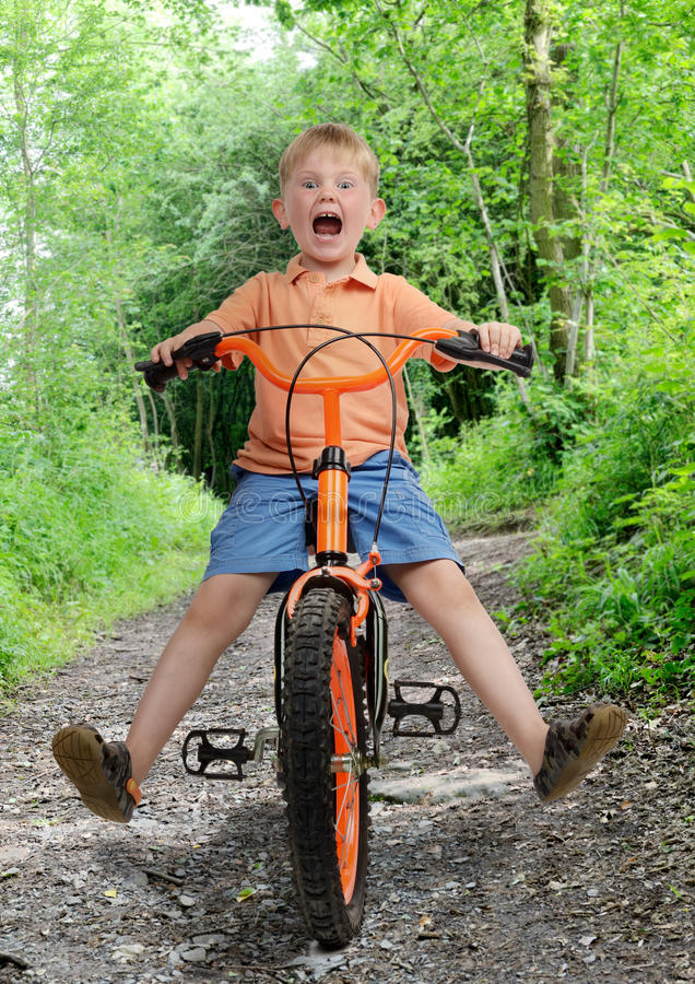 Bike crash. Young boy about to crash with a scared look on his face, isolated on a white background royalty free stock photography