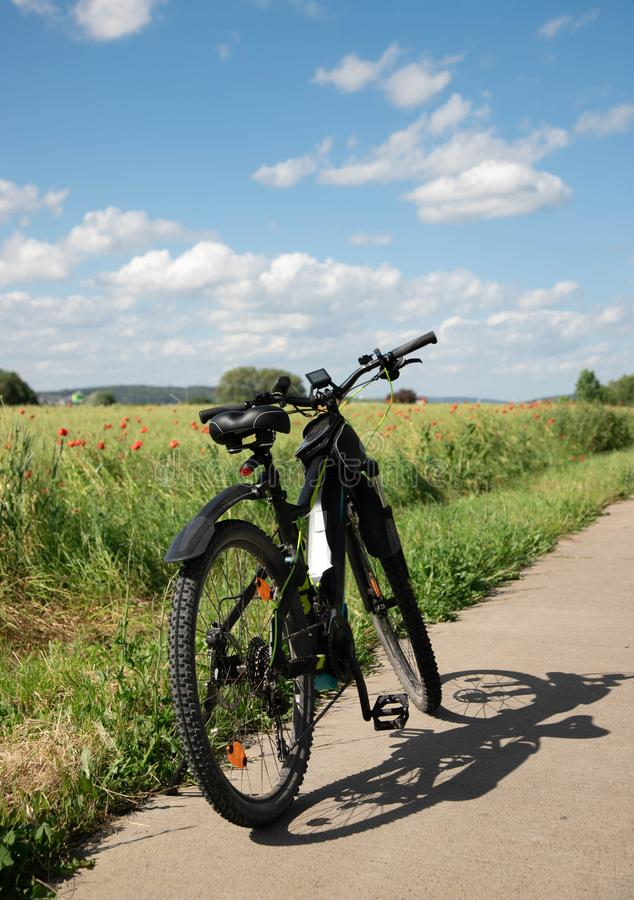 A bike, a bike with electric drive stands on a stone path next to the spring green field with red poppies. On far background, blue royalty free stock photos