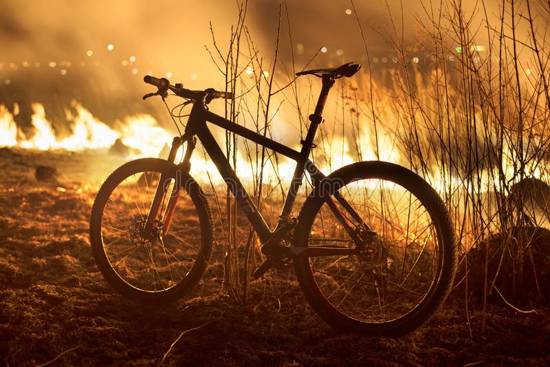 Bike on fire field. The fire in the field is hot and dangerous, its flame with heat and poisonous smoke, harmful to humans and animals and birds. Bike arriving stock image