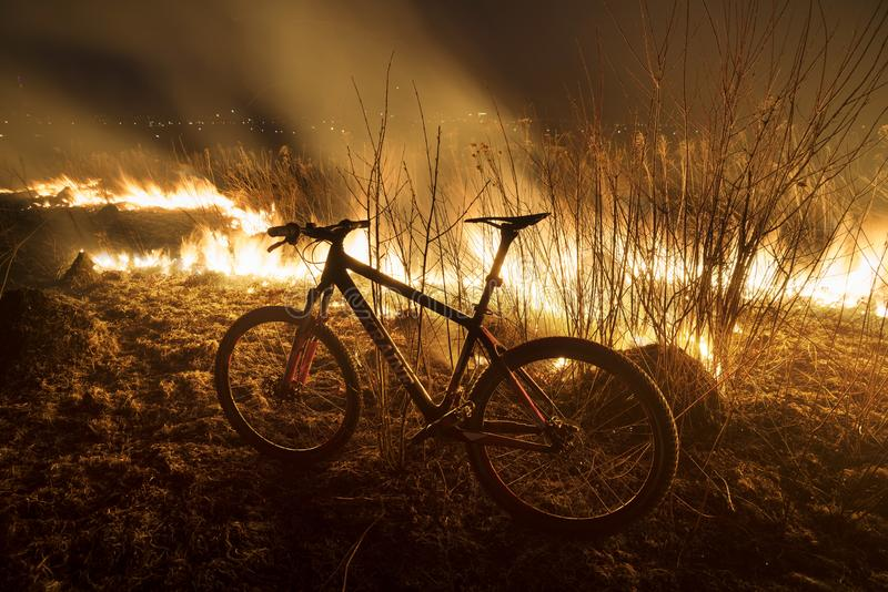 Bike on fire field. The fire in the field is hot and dangerous, its flame with heat and poisonous smoke, harmful to humans and animals and birds. Bike arriving royalty free stock image