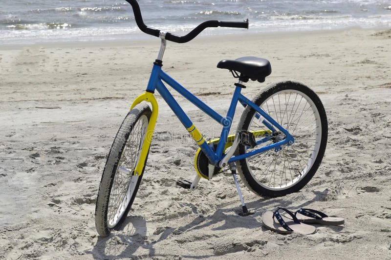 Bike and flip-flops at the beach stock image