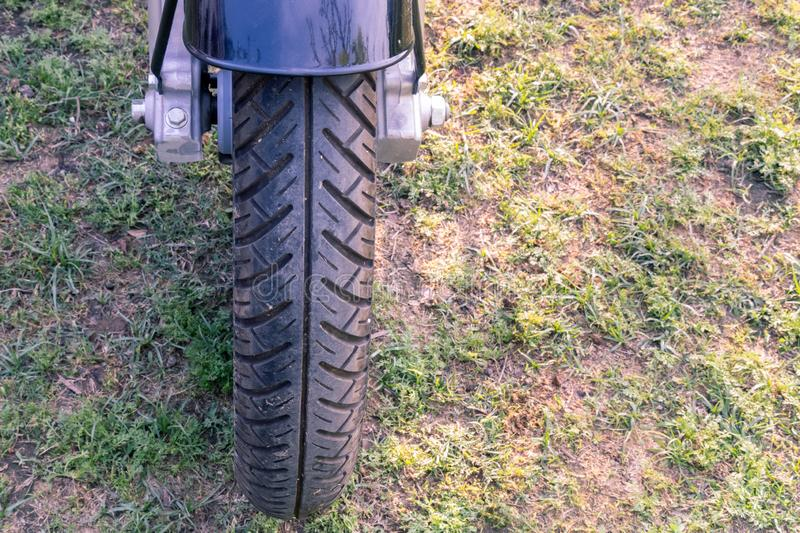 Bike front tire on green ground. Closeup view from front side royalty free stock photography