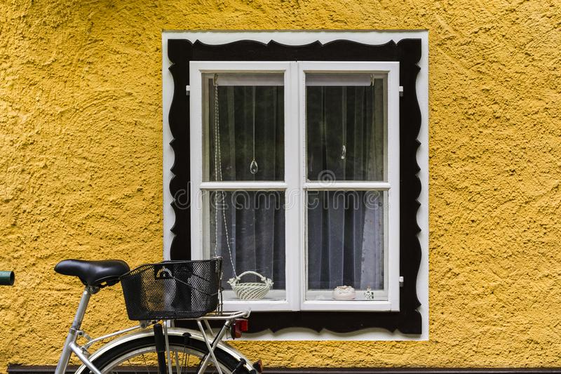 Bike at home in the Austrian city of Hallstatt. On a rainy day. Typical window of a house in a small town in Austria, architecture, street, bicycle, village royalty free stock image