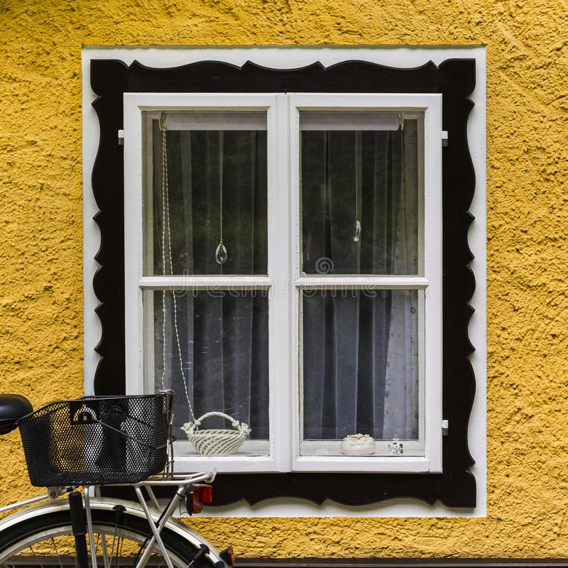 Bike at home in the Austrian city of Hallstatt. On a rainy day. Typical window of a house in a small town in Austria, architecture, street, bicycle, village stock image